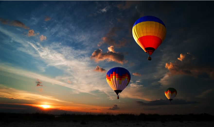 Three colourful hot air balloons flying at sunrise